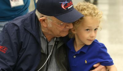 Eli Wilke, 6, gives Billings World War II veteran Donald Buska, left, a hug as he arrives at Dulles International airport in Dulles, Va. Buska fulfilled his longtime dream of traveling to Washington, Sunday, April 27, 2014, and over the visit he went to the National World War II Memorial with the help of Big Sky Honor Flight of Montana.  On Tuesday after returning to Montana, Buska, who had been in hospice care since Feb. 12, passed away. (AP Photo/The Billings Gazette, Lloyd Blunk)