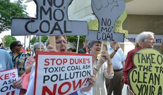Protesters carry signs and demonstrate in front of the Duke Energy office building in Charlotte, N.C., Thursday, May 1, 2014, as  shareholders hold their annual meeting. Some Duke Energy investors plan to push the utility's board of directors to investigate issues surrounding a massive coal ash spill that dumped toxic sludge into a 70-mile stretch of a North Carolina river. (AP Photo/The Charlotte Observer, T. Ortega Gaines) MAGS OUT; TV OUT; NEWSPAPER INTERNET ONLY (REV-SHARE)
