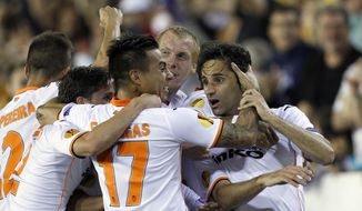 Valencia's  Jonas Gonzalves from Brazil, right, and Eduardo Vargas from Chile, left, Jeremy Mathieu from France, center, celebrates after scoring against Sevilla during their Europa League semifinal second leg soccer match at the Mestalla stadium in Valencia, Spain, Thursday, May 1, 2014. (AP Photo/Alberto Saiz)