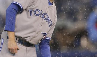 Toronto Blue Jays starting pitcher Drew Hutchison receives a ball from his catcher as rain begins to fall during the first inning of a baseball game against the Kansas City Royals at Kauffman Stadium in Kansas City, Mo., Wednesday, April 30, 2014. (AP Photo/Orlin Wagner)