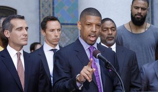 In this photo taken on April 29, 2014, Sacramento, Calif., Mayor Kevin Johnson, at podium, with Los Angeles Mayor Eric Garcetti, left, speaks about the penalties imposed on Los Angeles Clippers owner Donald Sterling by the NBA at a news conference at Los Angeles City Hall. From second left are current and former NBA players Steve Nash, Norm Nixon and Tyson Chandler. Last year Johnson almost single-handedly kept the Kings NBA franchise in Sacramento, staging a late-game comeback to snatch the team away from a Seattle billionaire. This spring he began raising his national political profile by taking over as the head of the U.S. Conference of Mayors, then acting as spokesman for the NBA players as the controversy over racist remarks by the Clippers' owner threatened to throw the basketball league into turmoil. (AP Photo/Nick Ut)