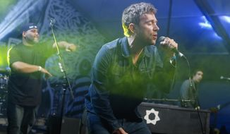 "FILE - In this March 14, 2014 file photo, Damon Albarn, right, joined by De La Soul's Vincent Mason, left, performs during the SXSW Music Festival in Austin, Texas. Albarn's new album, ""Everyday Robots,"" released on Monday, April 28, 2014. (Photo by Jack Plunkett/Invision/AP, file)"