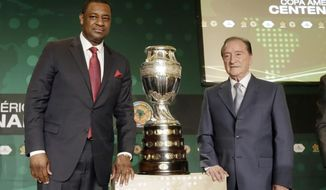 CONCACAF president Jeffrey Webb, left, and Eugenio Figueredo, right, president of CONMEBOL, the South American soccer confederation, pose for photographers next to the Copa America trophy during a news conference in Bal Harbour, Fla., Thursday, May 1, 2014. The United States will host the Copa America soccer tournament for the first time in 2016. The Copa America, the world's oldest intercontinental soccer tournament, will celebrate its 100th anniversary in 2016. (AP Photo/Alan Diaz)