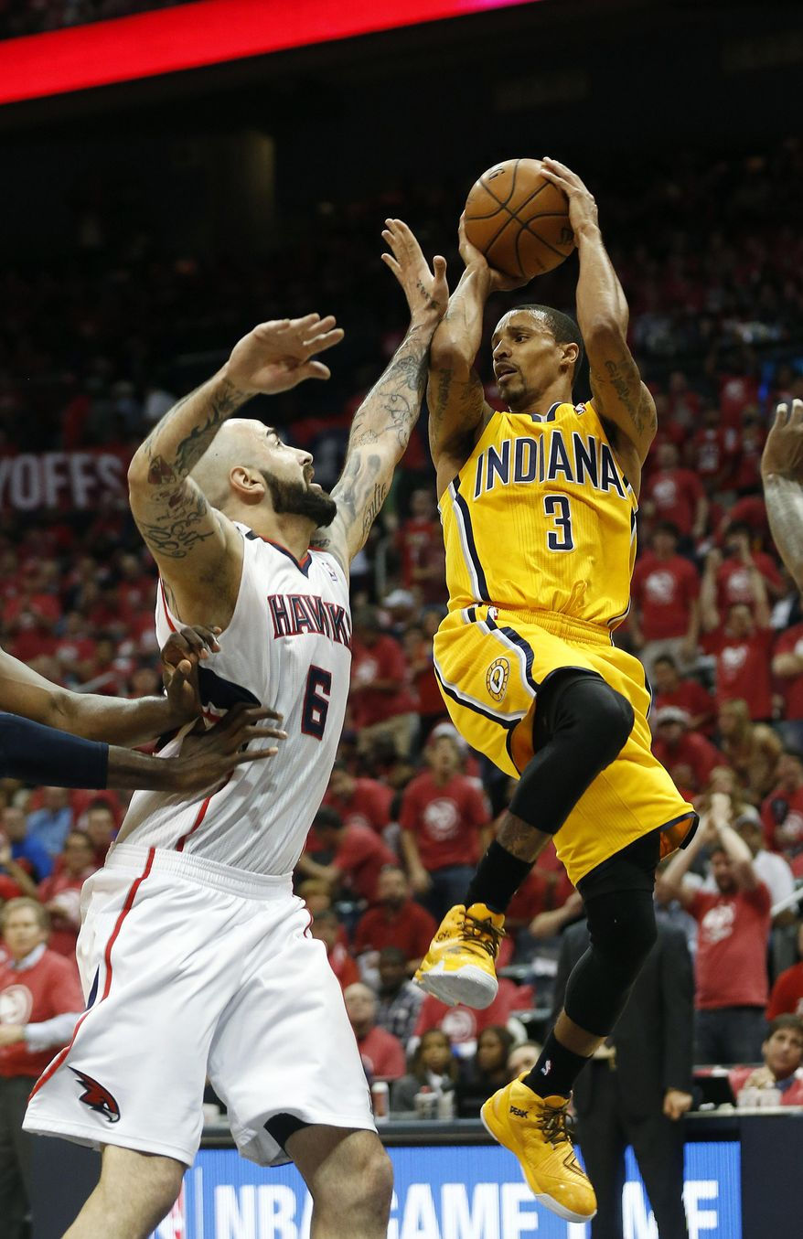 Indiana Pacers guard George Hill (3) passes as Atlanta Hawks center Pero Antic (6) defends in the first half of Game 6 of a first-round NBA basketball playoff series in Atlanta, Thursday, May 1, 2014. (AP Photo/John Bazemore)