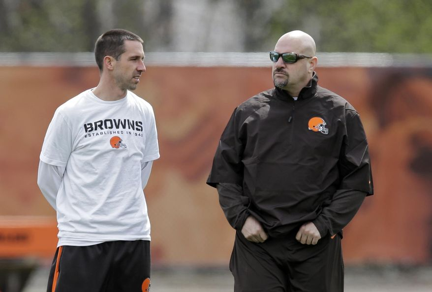 Cleveland Browns offensive coordinator Kyle Shanahan, left, talks with head coach Mike Pettine during a voluntary minicamp workout at the NFL football team's facility in Berea, Ohio Thursday, May 1, 2014. (AP Photo/Mark Duncan)