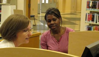 In this photo from Monday, March 31, 2014, Teresa Holmer, left, a health care navigator for the Shawnee County, Kan., Health Agency, counsels Topeka resident Tamika Terry about obtaining insurance coverage at the public library in Topeka, Kan. About 57,000 Kansas residents enrolled in health plans through the federal government's online health insurance marketplace. (AP Photo/John Hanna)