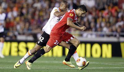 Valencia's Seydou Keita duels for the ball with Sevilla's Vitolo during their Europa League semifinal second leg soccer match at the Mestalla stadium in Valencia, Spain, Thursday, May 1, 2014. (AP Photo/Alberto Saiz)