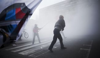 ** FILE ** Pro-Russian activists are seen in a tear gas cloud while throwing rocks at the prosecutor building, after a pro-Russia demonstration during International Worker's Day in Donestsk, Ukraine, Thursday, May 1, 2014. (AP Photo/Manu Brabo)