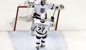 Los Angeles Kings goalie Jonathan Quick, top, celebrates a 5-1 win over the San Jose Sharks with teammate Alec Martinez (27) during Game 7 of an NHL hockey first-round playoff series on Wednesday, April 30, 2014, in San Jose, Calif. (AP Photo/Marcio Jose Sanchez)