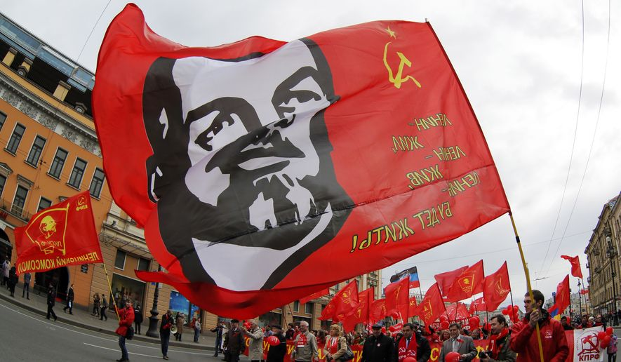 Communists carry a flag depicting Vladimir Lenin, the Soviet Union founder, during a traditional May Day march in St. Petersburg, Russia, Thursday, May 1, 2014. (AP Photo/Dmitry Lovetsky) ** FILE **
