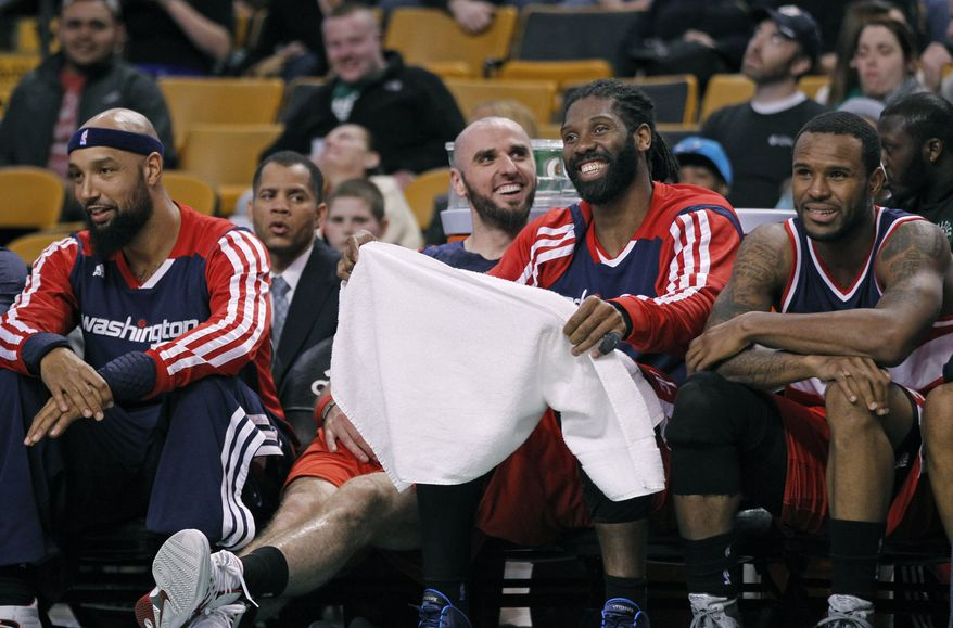 Washington Wizards players, from left, Drew Gooden, Marcin Gortat, Nene Hilario and Trevor Booker smile on the bench late in the fourth quarter of an NBA basketball game against the Boston Celtics in Boston, Wednesday, April 16, 2014. The Wizards clinched the No. 5 seed in the Eastern Conference with a 118-102 win over the Celtics and will face the Chicago Bulls in their first playoff appearance since 2008. (AP Photo/Elise Amendola)
