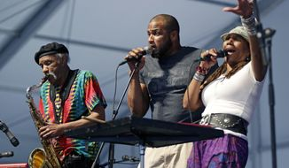 Charmaine Neville, right, performs with her son Damion Neville, center, and father Charles Neville at the New Orleans Jazz and Heritage Festival in New Orleans, Friday, May 2, 2014. (AP Photo/Gerald Herbert)