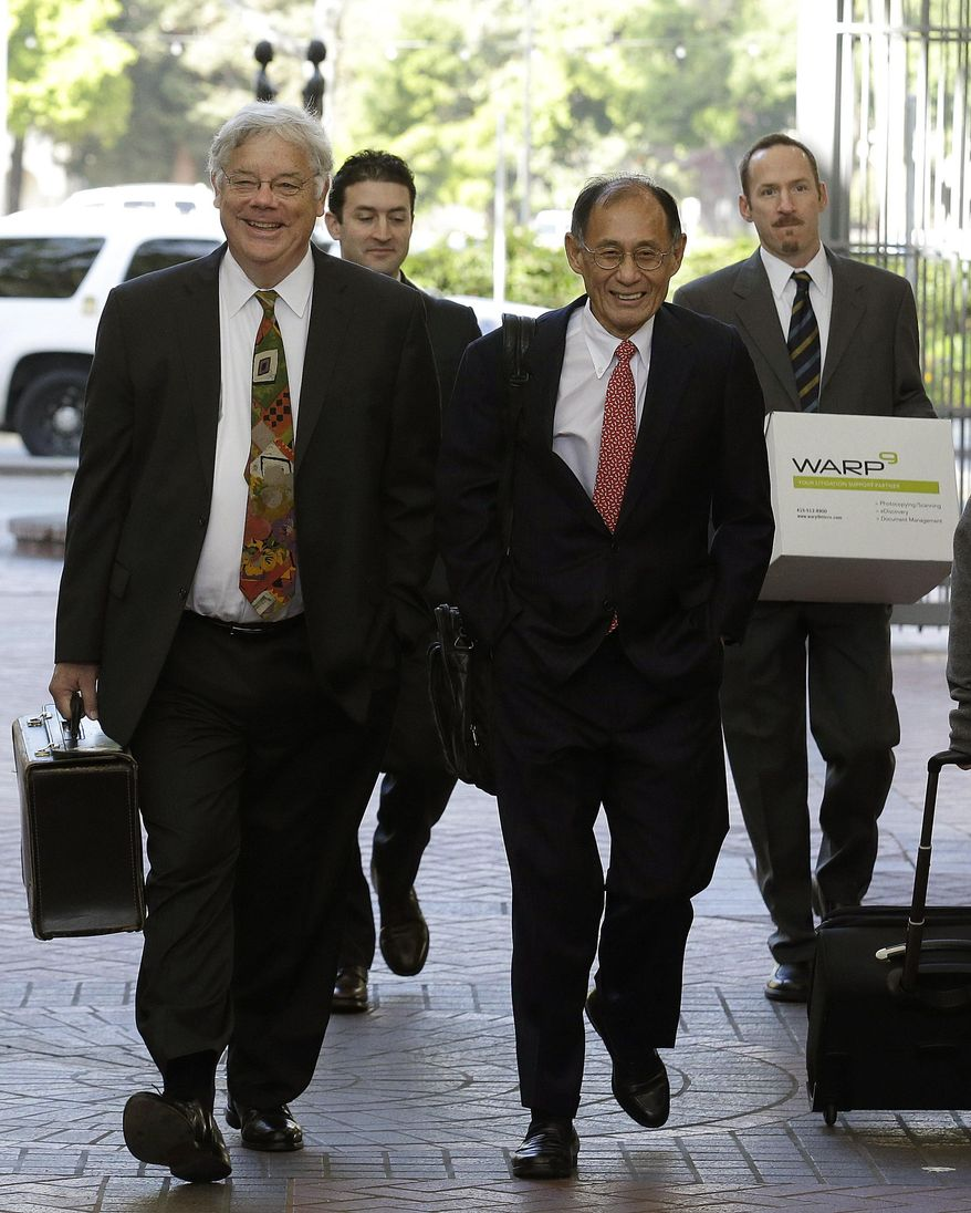 FILE - In this Monday, April 28, 2014, file photo,  Apple attorneys Harold McElhinny, left, and William Lee, walk with others to a federal courthouse in San Jose, Calif. A California jury determined Friday, May 2, 2014,  that Samsung infringed Apple smartphone patents and awarded $120 million damages.  (AP Photo/Jeff Chiu, File)