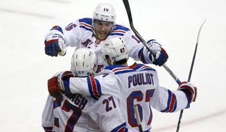 New York Rangers' Benoit Pouliot (67) celebrates his goal with teammates Ryan McDonagh (27) and Derick Brassard (16) in the first period of Game 1 of a second-round NHL hockey playoff series in Pittsburgh, Friday, May 2, 2014. (AP Photo/Gene J. Puskar)