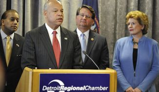 Homeland Security Secretary Jeh Johnson , Congressman Gary Peters, left,  and Senator Debbie Stabenow talks with Michigan state and local officials during a news conference on Friday, May 2, 2014 in Detroit.  Money is still being sought to fund a customs plaza for a planned $3.5 billion bridge between the United States and Windsor, Ontario, in Canada,  Johnson said.  The plaza is a vital part of the planned commuter bridge to span the Detroit River, linking Detroit to Windsor. The Canadian government is funding most of the bridge, expected to open in 2020.  (AP Photo/Detroit News, Daniel Mears)  DETROIT FREE PRESS OUT; HUFFINGTON POST OUT