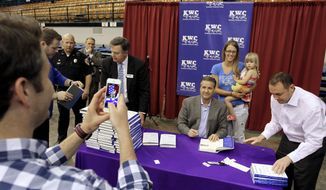 In this April 22, 2014 photo, Justin Weaver, left, of Owensboro, Ky., takes a photo of Kentucky NCAA college basketball coach John Calipari, sitting, and Corey Millay and her daughter Adalyn, 2, at a book signing in Owensboro, Ky. (AP Photo/The Messenger-Inquirer, Greg Eans)