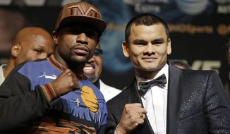 Floyd Mayweather Jr., left, and Marcos Maidana pose for photos during a news conference Wednesday, April 30, 2014, in Las Vegas. The pair square off in a welterweight title fight on Saturday, May 3.  (AP Photo/Isaac Brekken)
