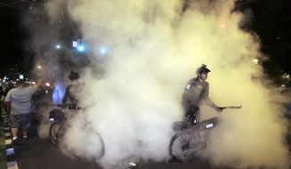 Police extinguish burning signs during May Day activities Thursday, May 1, 2014 in Seattle. Police have made several arrests and fired pepper spray as anti-capitalist marchers meandered through Seattle several hours after hundreds of peaceful demonstrators took part in a May Day march in support of immigrant rights and a boost in the minimum wage. (AP Photo/Ted S. Warren)