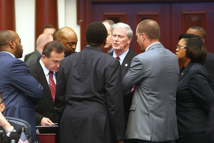 Florida Senator John Thrasher, center, has a heated discussion on the floor of the House, Friday night, with House Democrats and Rep. Robert Schenck, R- Spring Hill at the start of a debate on a school voucher bill, Friday, May 2, 2014. (AP Photo/The Tampa Bay Times, Scott Keeler)