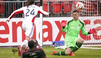 Toronto FC defender Doneil Henry (15) tackles New England Revolution forward Lee Nguyen (24) as goalkeeper Julio Cesar makes a save during the second half of an MLS soccer game in Toronto on Saturday, May 3, 2014. (AP Photo/The Canadian Press, Frank Gunn)