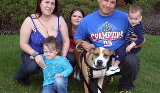 """The James family of Eatontown who found their dog """"Reckless"""" a year and half after losing it during Superstorm Sandy. Here the family poses for a photograph in Neptune.  Chuck James, center, with """"Reckless"""" and wife Elicia, left,  and children Kelsey, left, Ally, center, and Liam, on knee. (AP Photo/The Asbury Park Press, Mark R. Sullivan)  Mark R. Sullivan/staff photographer  On Friday May 2,2014 Neptune"""