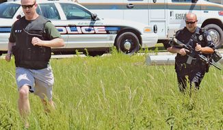 Drug Task Force Detective Josh Talbott, left, and Jonesboro Police Department Patrolman First Class Duane Busby run across a field adjacent to Moore Road while responding to a Saturday, May 3, 2014 shooting in Jonesboro, Ark. A gunman shot six people at an Arkansas home Saturday, killing a man and a teenager and critically wounding two boys, before fatally shooting a worker at a nearby business, police said. (AP Photo/The Jonesboro Sun, Sarah Morris)