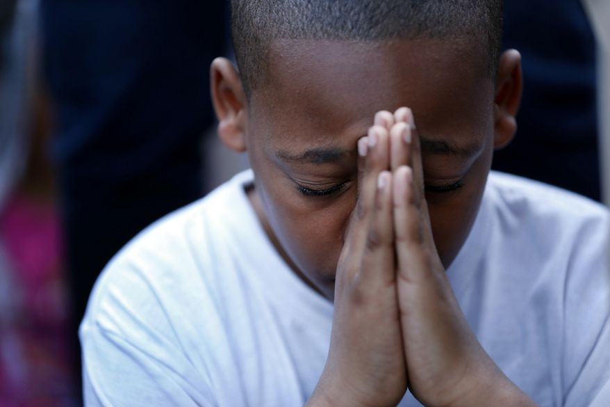 A young boy folds his hands in prayer during a prayer vigil for Martin Cobb at Abundant Life Church on Richmond's south side  Saturday, May 3, 2014. A 16-year-old boy was charged Saturday in the assault of a young girl and the killing of Martin, her brother, who was apparently slain when he tried to protect her, authorities and relatives said. (AP Photo/Richmond Times-Dispatch, Dean Hoffmeyer)