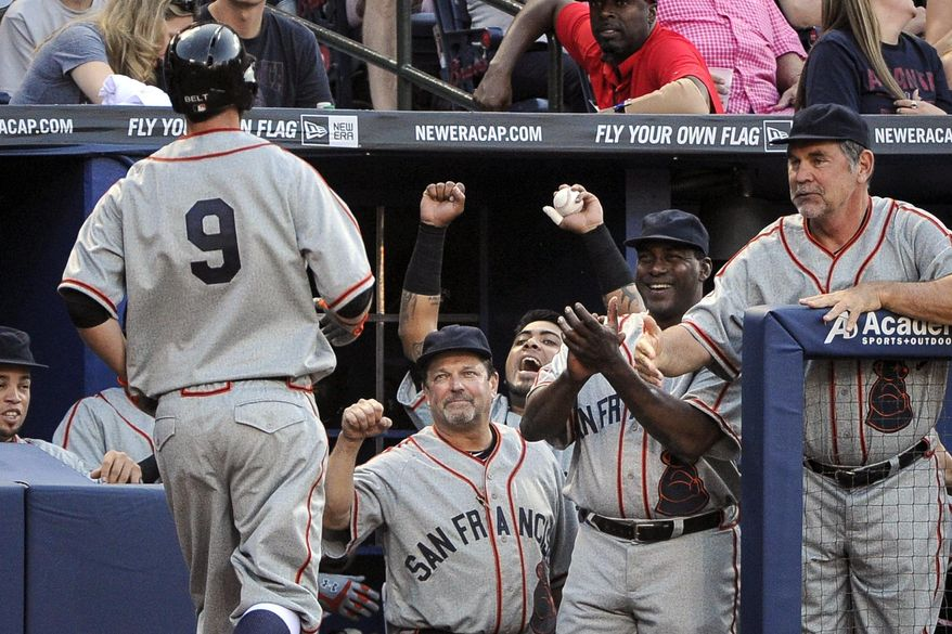 San Francisco Giants teammates celebrate as first baseman Brandon Belt (9) approaches the dugout on a home run against the Atlanta Braves during the second inning of a baseball game, Saturday, May 3, 2014, in Atlanta. (AP Photo/John Amis)