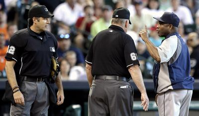 Seattle Mariners manager Lloyd McClendon, right, has more to say after being ejected by home plate umpire James Hoye, left, as umpire Bob Davidson steps in during the seventh inning of a baseball game on Saturday, May 3, 2014, in Houston. (AP Photo/Pat Sullivan)