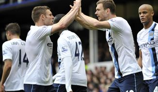 Manchester City's Edin Dzeko, right, celebrates with teammate James Milner after scoring the second goal of the game during their English Premier League soccer match against Everton at Goodison Park in Liverpool, England, Saturday May 3, 2014. (AP Photo/Clint Hughes)