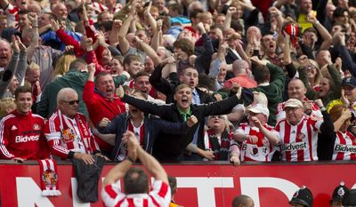 Jubilant Sunderland supporters celebrate a goal by Sebastian Larsson during their English Premier League soccer match against Manchester United at Old Trafford Stadium, Manchester, England, Saturday May 3, 2014. (AP Photo/Jon Super)