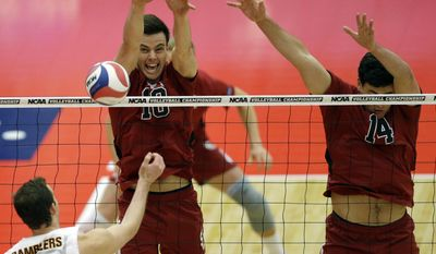 Stanford's Brian Cook (10) and Spencer Haly (14), right, block the ball hit by Loyola's Cody Caldwell (12) during the first set of the NCAA men's college volleyball championship at Gentile Arena in Chicago on Saturday, May 3, 2014. (AP Photo/Nam Y. Huh)