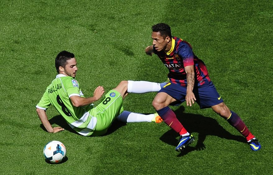 FC Barcelona's Adriano, from Brazil, right, duels for the ball against Getafe's Pablo Sarabia during a Spanish La Liga soccer match at the Camp Nou stadium in Barcelona, Spain, Saturday, May 3, 2014. (AP Photo/Manu Fernandez)