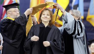 General Motors CEO Mary Barra, center, is conferred an honorary Doctor of Engineering degree before addressing the University of Michigan graduates at a commencement ceremony Saturday, May 3, 2014 in Ann Arbor, Mich. Barra, the first woman to lead a major automaker, took the top spot at GM in January, just as a deadly ignition switch problem was starting to surface. Barra urged the students to be honest in every aspect of their lives, and to use their optimism and propensity for inclusion to rethink outdated assumptions and expose and correct injustice. (AP Photo/Carlos Osorio)