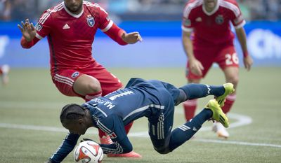 Vancouver Whitecaps FC's Darren Mattocks, center, fights for control of the ball with San Jose Earthquakes' Victor Bernardez, left, and Brandon Barklage, right, during the first half of an MLS soccer game action in Vancouver, Saturday, May, 3, 2013. (AP Photo/The Canadian Press, Jonathan Hayward)