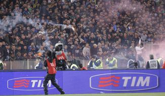 Napoli fans throw flares prior to the start of Italian Cup final match between Fiorentina and Napoli in Rome's Olympic stadium Saturday, May 3, 2014. At least one fan and one police officer were reportedly shot before the Italian Cup final between Napoli and Fiorentina, and the fan was in serious condition. As a result, the start of the final was delayed, and there were scenes of violence inside the stadium with a firefighter injured by fireworks thrown from the stands. The shootings occurred in an area where Napoli fans were gathering for the match, the ANSA news agency reported. (AP Photo/Gregorio Borgia)