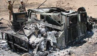 In this Thursday, May 1, 2014 photo provided by Yemen's Defense Ministry, soldiers inspect the wreckage of a vehicle destroyed during fighting with al-Qaida militants in Majala of the southern province of Abyan, Yemen. (AP Photo/Yemen's Defense Ministry)