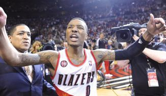Portland Trail Blazers' Damian Lillard, center, celebrates with fans, his winning shot against the Houston Rockets during the last .9 of a second of game six of an NBA basketball first-round playoff series game in Portland, Ore., Friday May 2, 2014. The Trail Blazers won the series in a 99-98 win. (AP Photo/Greg Wahl-Stephens)