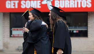 Soon to be University of Michigan graduates hug in front of a burrito restaurant before walking to Michigan Stadium for the university's spring commencement in Ann Arbor, Mich. Saturday, May 3. (AP Photo/The Ann Arbor News, Brianne Bowen)