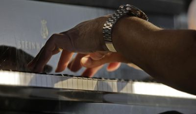 Ellis Marsalis, father and musical teacher of his sons, artists Wynton Marsalis, Branford Marsalis, Jason Marsalis and Delfeayo Marsalis, performs at the New Orleans Jazz and Heritage Festival in New Orleans, Saturday, May 3, 2014. (AP Photo/Gerald Herbert)