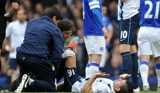 Manchester City's Sergio Aguero receives treatment on the pitch during their English Premier League soccer match against Everton at Goodison Park in Liverpool, England, Saturday May 3, 2014. (AP Photo/Clint Hughes)