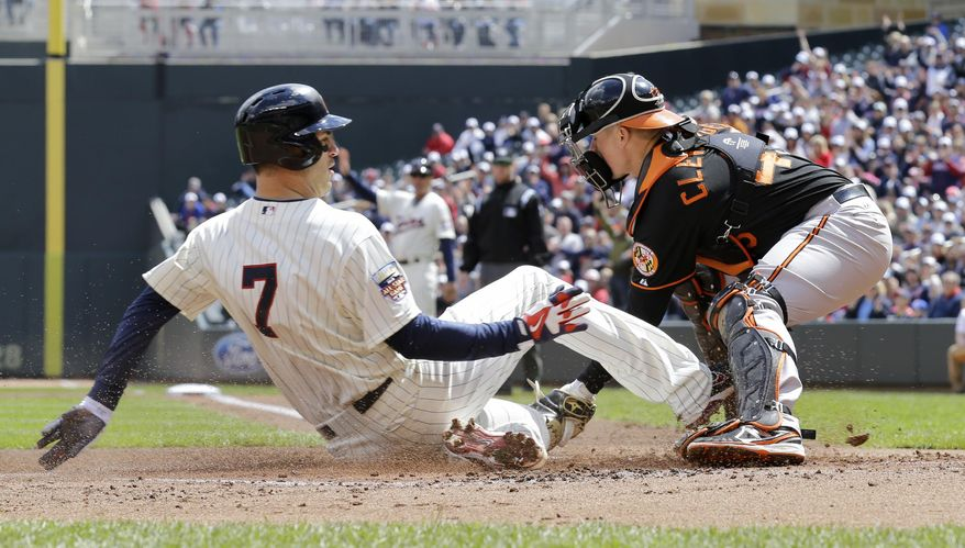 Minnesota Twins' Joe Mauer (7) scores from first base on a double by Twins' Trevor Plouffe as Baltimore Orioles catcher Steve Clevenger, right, waits for the throw from center field during the first inning of a baseball game in Minneapolis, Saturday, May 3, 2014. (AP Photo/Ann Heisenfelt)