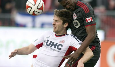 Toronto FC's defender Doneil Henry. right, and New England Revolution forward Patrick Mullins battle for a header during the first half of an MLS soccer game in Toronto on Saturday, May 3, 2014. (AP Photo/The Canadian Press, Frank Gunn)