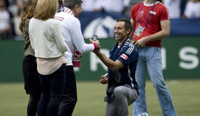 Vancouver Whitecaps FC part-owner Steve Nash, right, drops to one knee as he presents Bob Lenarduzzi with a ring commemorating the 1974 Vancouver Whitecaps team before a MLS soccer game against the San Jose Earthquakes in Vancouver, Saturday, May, 3, 2013. (AP Photo/The Canadian Press, Jonathan Hayward)