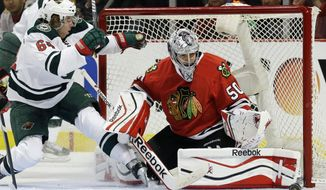 Chicago Blackhawks goalie Corey Crawford (50) blocks a shot by Minnesota Wild's Mikael Granlund (64) during the first period in Game 1 of an NHL hockey second-round playoff series in Chicago, Friday, May 2, 2014. (AP Photo/Nam Y. Huh)