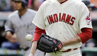 Cleveland Indians relief pitcher John Axford gets a new ball after giving up a three-run home run to Chicago White Sox's Dayan Viciedo in the ninth inning of a baseball game Sunday, May 4, 2014, in Cleveland. Axford took the loss as Chicago won 4-3. (AP Photo/Mark Duncan)