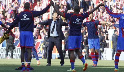 Levante's coach Joaquin Caparros and his players celebrate their victory against Atletico de Madrid at theCiutat de Valencia stadium in Valencia, Spain, on Sunday, May 4, 2014. (AP Photo/Alberto Saiz)
