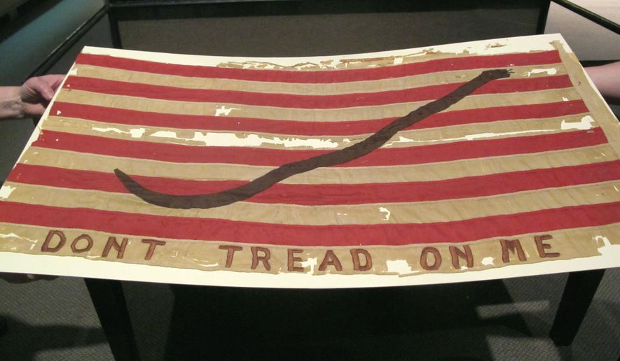 An American naval flag that could date to the Revolutionary War is seen at the Charleston Museum in Charleston, S.C., on April 30, 2014. The flag is part of a new exhibit of flags at the museum, that opens on May 5, 2014. Experts at the museum say they don't have enough information to accurately date the flag that could be from the Revolution or perhaps created during the centennial of the Revolution in the 1870s. (AP Photo/Bruce Smith)