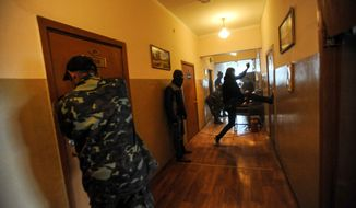 Masked demonstrators break into storerooms inside the military prosecutor's office in Donetsk. Pro-Russian forces and their supporters have been seizing and ransacking government buildings across eastern Ukraine. (Associated Press)