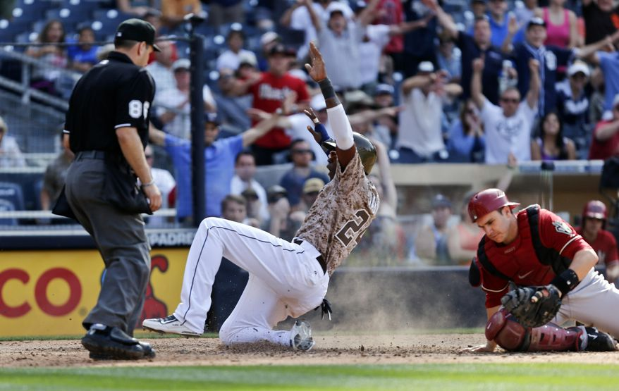 San Diego Padres' Cameron Maybin, center, raises his arms at home with the winning run as Arizona Diamondbacks catcher Miguel Montero, right, is too late to make a tag and home plate umpire is David Rackley watches in the bottom of the ninth inning of a baseball game on Sunday, May 4, 2014, in San Diego.  The Padres won 4-3. (AP Photo/Lenny Ignelzi)